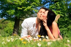 Paar liegt auf der Wiese und küsst sich