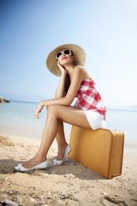 Frau sitzt auf einem Koffer am Strand
